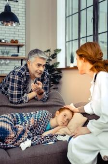 Professioneel advies. aangename knappe man die naar de dokter kijkt terwijl hij haar vraagt naar de toestand van haar dochters