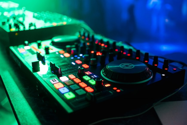 Professioneel bedieningspaneel en het mixen van muziek onder de groene lichten in nachtclub op feestje