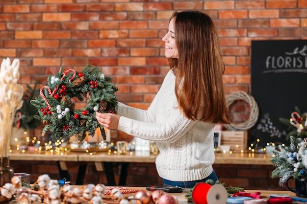 Professioneel bloemistenbedrijf. vrolijke dame met decoratieve dennenboom krans, glimlachend.