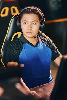 Professioneel cybersport-gamerportret van een jonge aziatische man met een koptelefoon die opzij kijkt terwijl