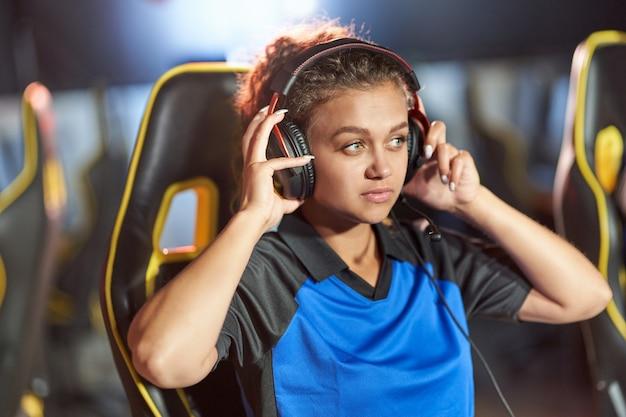 Professioneel cybersport tienermeisje van gemengd ras met een koptelefoon die online videogames speelt