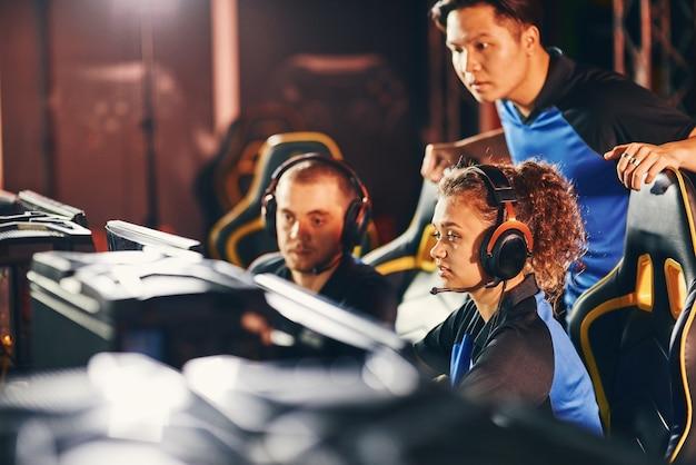 Professioneel cybersportteam twee jonge jongens en meisje kijken naar pc-scherm praten en discussiëren