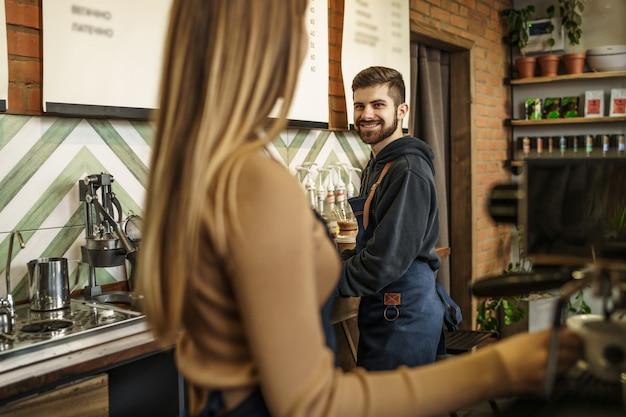 Professioneel en gelukkig barista-team dat koffie zet met koffiemachine in coffeeshop