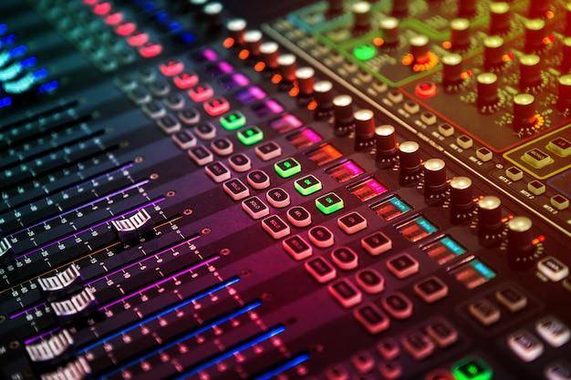 Professioneel geluids- en audiomixerbedieningspaneel met knoppen en schuifregelaars