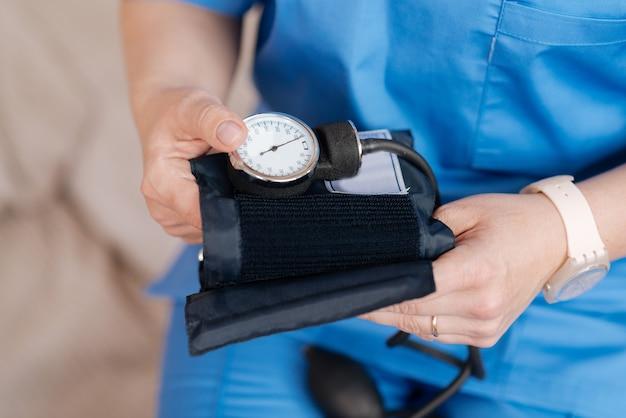 Professioneel gereedschap. hardwerkende, nette, ijverige verpleegster die medische apparatuur wil gebruiken om de bloeddruk van patiënten te lezen en zijn algehele gezondheidstoestand te controleren