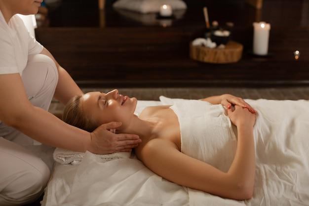 Professioneel geschoolde masseuse. stralende goed uitziende bezoeker van spa-centrum genietend van ervaren bewegingen van sterke masseuse