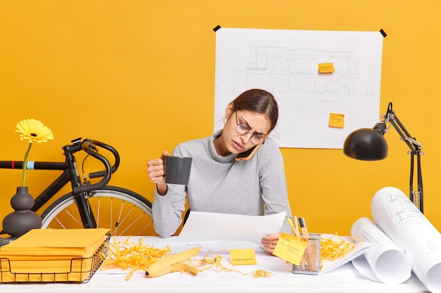 Professioneel geschoolde vrouwelijke architect heeft telefoongesprek met collega geconcentreerd in papieren bereidt engineering project drinkt koffie poses in coworking space. drukke vrouwelijke ingenieur