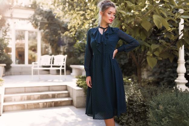 Professioneel model poseren in de achtertuin van het restaurant, groene jurk dragen, hand op de taille, tuin, buiten, make-up, haarbroodje, rode lippen