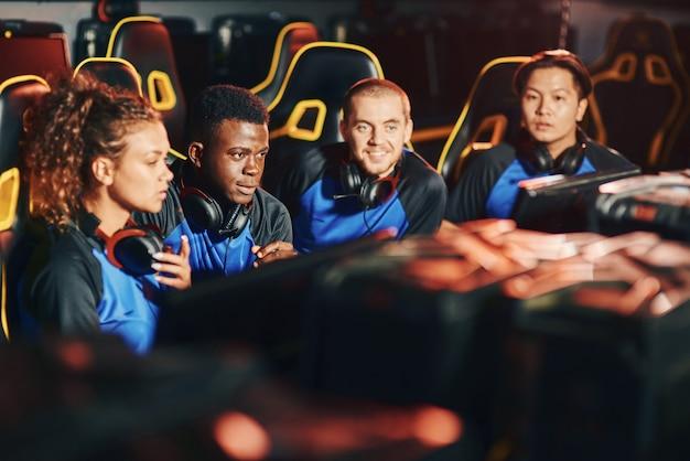 Professioneel multiraciaal cybersportteam dat samen zit in een gamingclub of internetcafé, terwijl ze naar pc-schermen kijken terwijl ze deelnemen aan een esport-toernooi. competitie voor online videogames