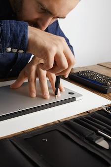 Professioneel nauwkeurig losschroeven van behuizing van metalen dunne laptop in zijn elektrische servicelaboratorium in de buurt van gereedschapstas om deze schoon te maken en te repareren
