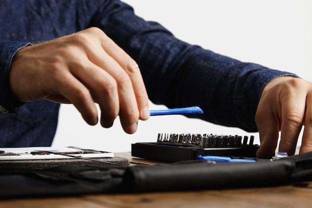 Professioneel neemt een speciaal plastic instrument uit zijn gereedschapstas mee naar de reparatietablet
