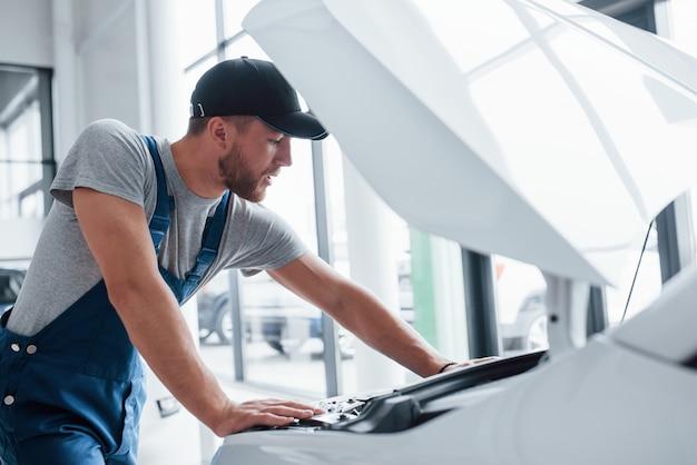 Professioneel op het werk. man in blauw uniform en zwarte hoed beschadigde auto repareren