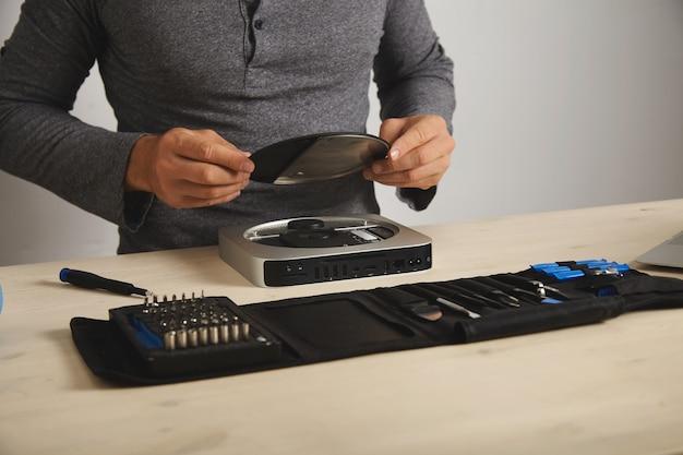 Professioneel opent topkoffer van kleine personal computer voordat het geheugen wordt geüpgraded, brede kijkhoek