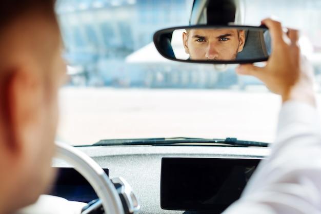 Professioneel rijden. zelfverzekerde slimme man op zoek in de achteruitkijkspiegel tijdens het besturen van zijn auto