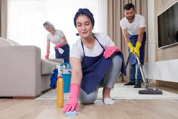 Professioneel schoonmaakserviceteam reinigt woonkamer in modern appartement