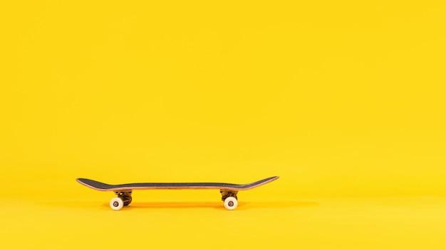 Professioneel skateboard geïsoleerd op gele achtergrond.