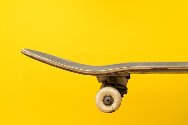 Professioneel skateboard op geel oppervlak zijaanzicht.