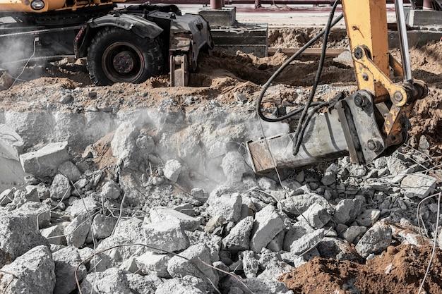 Professioneel slopen van constructies van gewapend beton met behulp van industriële hydraulische hamer met graafmachine. staven van metalen hulpstukken. wrakstukken en brokstukken van beton.