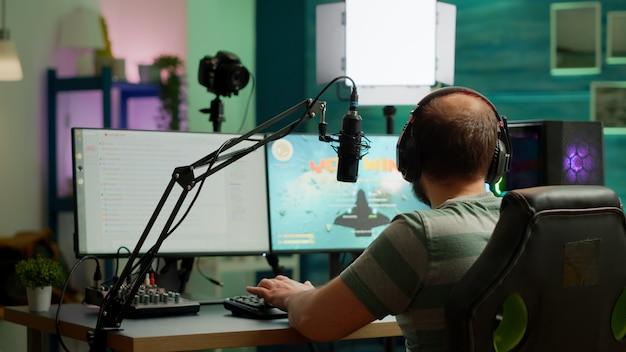Professioneel streamer-winnende space shooter-videogame bij live competitie spelen vanuit thuisstudio. online streaming cyber optreden tijdens gametoernooien met krachtige computer met rgb-verlichting