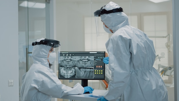 Professioneel tandheelkundig personeel met pbm-pak dat naar röntgenfoto's van tanden kijkt
