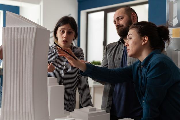 Professioneel team van architecten die maquette analyseren