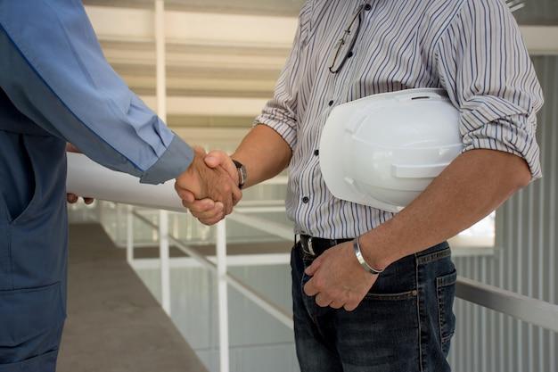 Professioneel techniekteam met witte helm die handen aan elkaar schudden