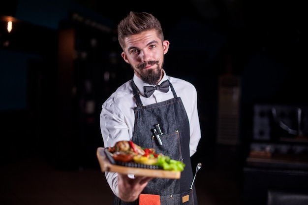 Professioneel vriendelijke flunky houdt behulpzaam bord met bereide schotel vast bij een feestelijk evenement.