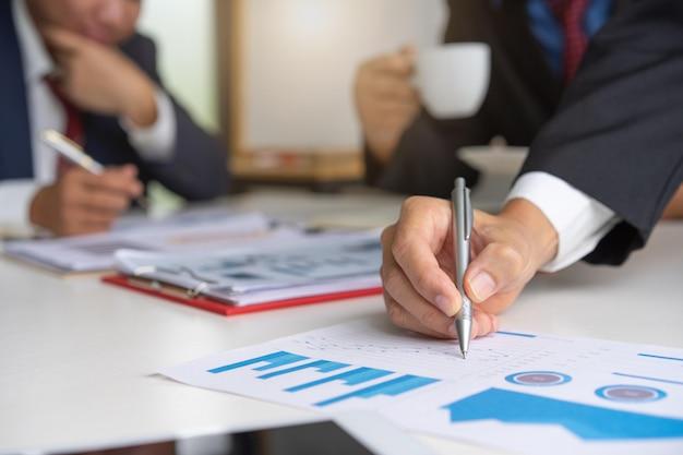 Professioneel zakenlui die samen en aan vennootschap in conferentieruimte tijdens vergadering op kantoor verklaren bespreken.