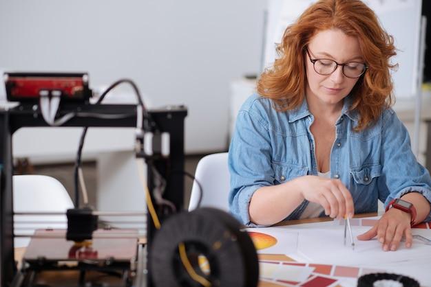 Professionele aardige slimme vrouw die een kompas vasthoudt en een tekening doet terwijl ze werktekeningen maakt