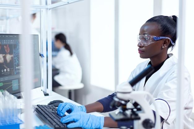 Professionele afrikaanse medische werker die informatie typt over virusstudie zwarte gezondheidswetenschapper in biochemisch laboratorium met steriele apparatuur.