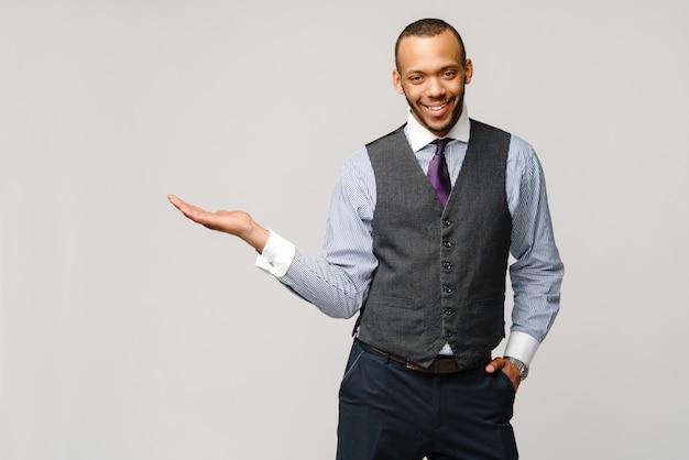 Professionele afro-amerikaanse zakenman - presenteren wijst een hand op kopie ruimte.