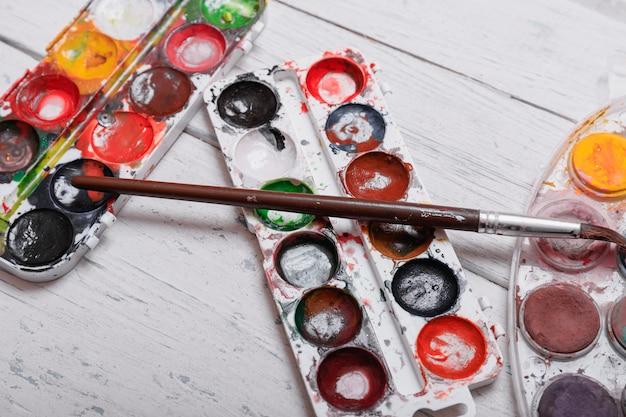 Professionele aquarel aquarell verf in doos met borstels op oude witte houten bord