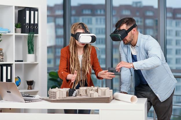 Professionele architect die bij bureau werkt en een vr-hoofdtelefoon draagt, bekijkt hij een virtual reality-interface