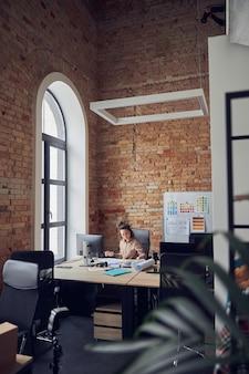 Professionele architect of ontwerper die druk bezig is tijdens het werken aan een blauwdruk aan tafel