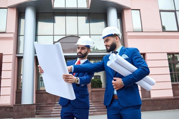 Professionele architecten die samen buiten een bouwplan doornemen voor een zakencentrum