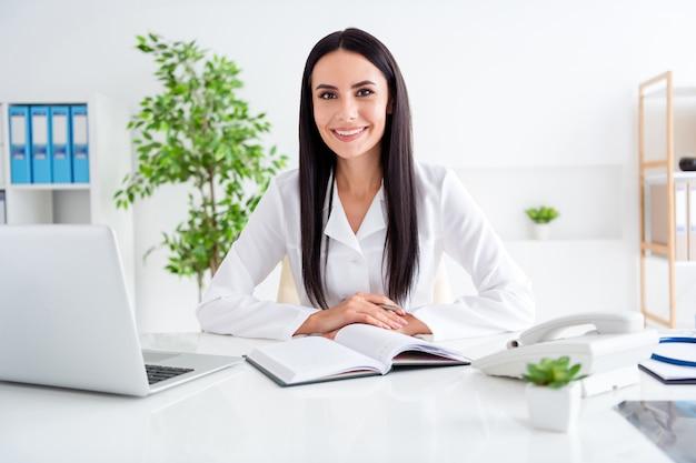 Professionele arts dame zit in de kliniek van het medisch centrum