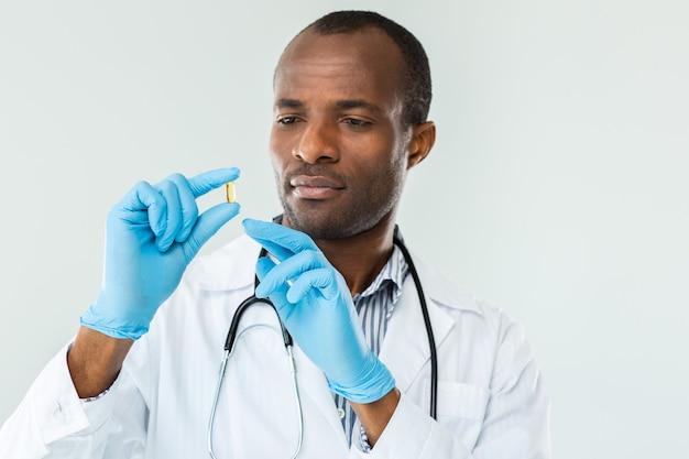 Professionele arts die een pil vasthoudt terwijl hij ernaar kijkt