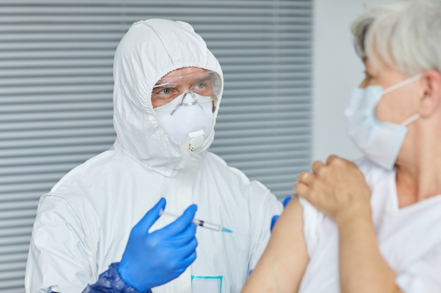 Professionele arts die handschoenen draagt die antivirale injectie geven aan oude vrouw die voor hem in ziekenhuisafdeling zit