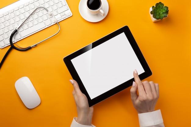 Professionele arts die medische dossiers in een digitale tablet met stethoscoop, toetsenbord, koffiekop en muis schrijft