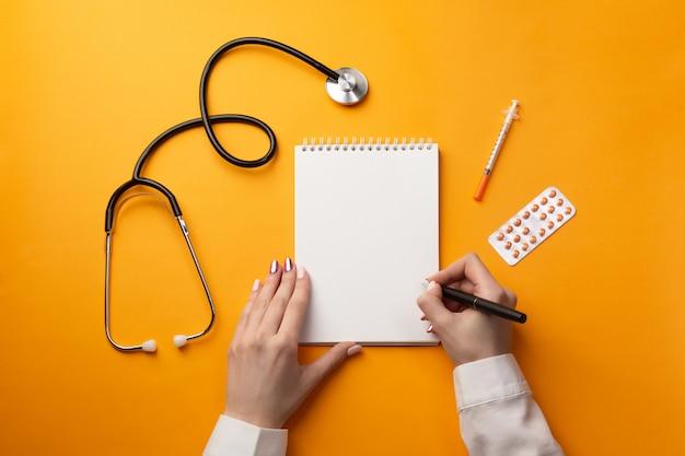Professionele arts die medische dossiers in een notitieboekje met stethoscoop, spuit en pillen schrijft