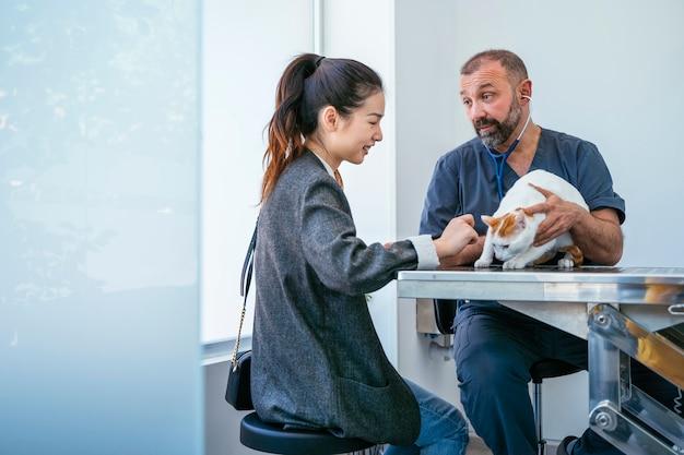 Professionele arts die ziek symptoom van een ziek huisdier uitlegt aan een bezorgde vrouw.