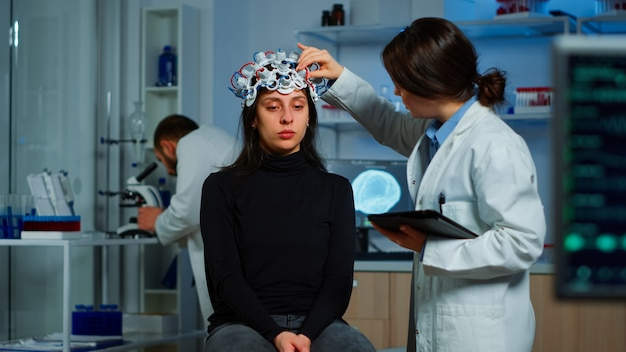 Professionele arts in de neurowetenschappen die een behandeling ontwikkelt voor neurologische ziekten die de evolutie van de patiënt onderzoekt. arts-onderzoeker die eeg-headset aanpast die hersenfuncties en gezondheidsstatus analyseert