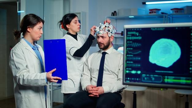 Professionele arts in neurologische geneeskunde wijzend op klembord testen gezichtsvermogen van man met eeg headset