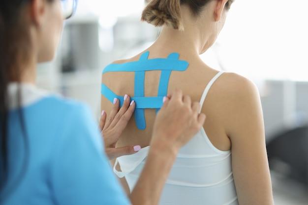 Professionele arts legde tapes op de rug van de patiënt voor een effectieve behandeling van scoliose en pijnverlichting.