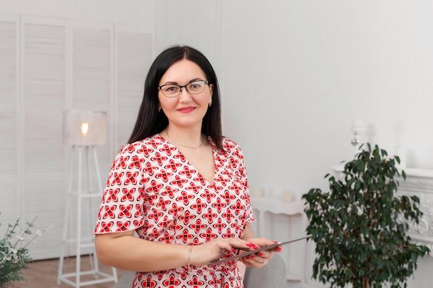 Professionele arts psycholoog met een bril in een heldere kantoor met een tablet
