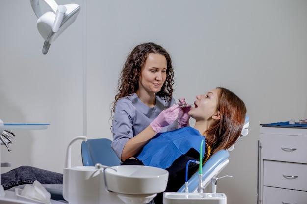 Professionele arts-tandarts onderzoekt en behandelt verwende tanden