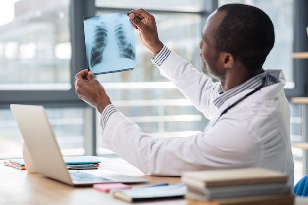 Professionele arts zittend in halve positie terwijl het verhogen van de armen, document controleren
