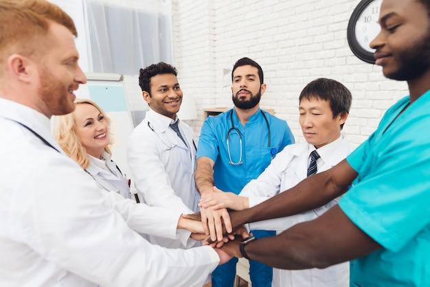 Professionele artsen die elkaar handen houden.
