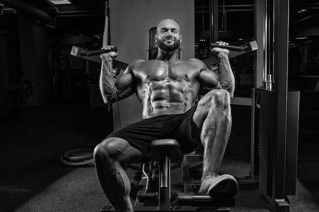 Professionele atleet doet schoudertraining in de sportschool. bodybuilding, fitness, sportconcept. gemengde media