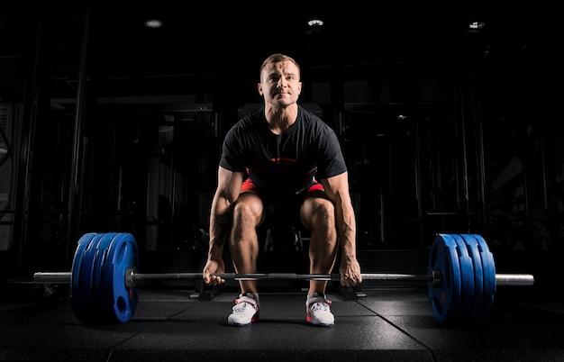 Professionele atleet gebogen over de halter en bereidt zich voor om een zeer zwaar gewicht op te tillen.